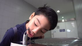 Asian hungry boy drinking water from water tube. stock video