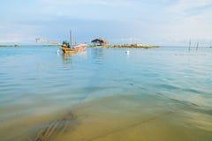 Asian idyllic coastal scene with traditional long tail fishing b Royalty Free Stock Photos