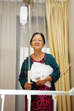 Asian ill old woman portrait in hospital ward. Asian ethnic sick senior patient portrait in hospital ward holding lab result Royalty Free Stock Photography