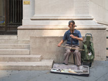 Asian immigrant playing an instrument for money in New York Stock Photo