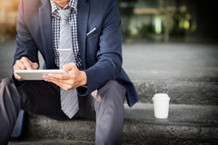 Asian Indian businessman using tablet pc outdoors, golden sunlig Royalty Free Stock Photography
