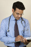 Asian Indian Doctor writing a report Royalty Free Stock Image