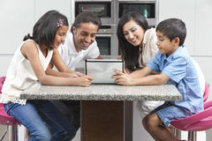 Asian Indian Family Using Tablet Computer at Home. Asian Indian family husband & wife, children, girl and boy, using tablet computer in the kitchen at home royalty free stock image