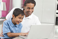 Asian Indian Father & Son Using Laptop Computer. Asian Indian father and son, men and boy, using laptop computer in the kitchen at home stock photos