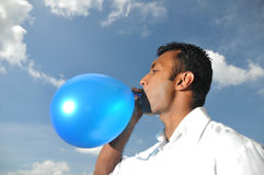 Asian Indian Man blowing balloon outdoor Royalty Free Stock Image