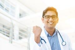 Asian Indian medical doctor celebrating success. Portrait of successful Asian Indian medical doctor smiling and celebrating success, standing outside hospital Royalty Free Stock Photography
