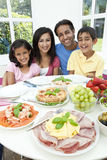 Asian Indian Parents Children Family Eating Meal. An attractive happy, smiling Asian Indian family of mother, father, son and daughter eating healthy food & royalty free stock photo