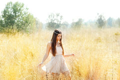 Asian indian woman walking in golden dried field Stock Photos