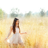 Asian indian woman walking in golden dried field Royalty Free Stock Images