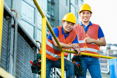Asian Indonesian construction workers. With helmet and safety vest on a building site in Asia Stock Image