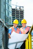 Asian Indonesian construction workers on building site. Asian Indonesian construction workers with blueprint or plan on building site Stock Photo