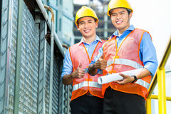Asian Indonesian construction workers on building site. Asian Indonesian construction workers with blueprint or plan on building site Royalty Free Stock Image
