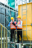Asian Indonesian construction workers on building site. Asian Indonesian construction workers with helmet and safety vest on a building or industrial site in Royalty Free Stock Photos