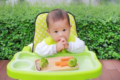 Asian infant baby boy eating by Baby Led Weaning BLW. Finger foods concept.  royalty free stock images