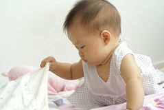Asian infant finding item under a blanket. Royalty Free Stock Images