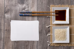 Asian ingredients and sticks. Asian table prepared with chopsticks, soy sauce and rice and white note for writing Stock Images