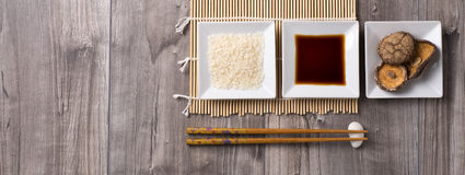 Asian ingredients table with chopsticks, rice, soy sauce and shitake mushrooms. Asian table prepared with chopsticks, rice, soy sauce and shitake mushrooms on Royalty Free Stock Photos