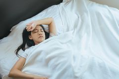 Asian insomnia woman have a headache on bed. Asian insomnia young woman have a headache on bed Royalty Free Stock Photos