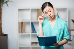 Asian internist looking at clipboard with diagnosis in professional clinic Royalty Free Stock Image