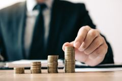 Asian investors man are placing coins in a growing position with savings finance money concept stock photos