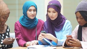 Asian Islamic women sharing info from smartphone during their visit a seminar. Asian Islamic women in bright hijabs sharing info from smartphone during their stock video footage