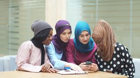 Asian Islamic women sharing info from smartphone during their visit a seminar. Asian Islamic women in bright hijabs sharing info from smartphone during their stock footage