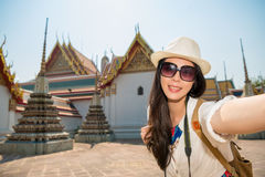 Asian japanese woman taking self portrait. Selfie photo with smartphone camera on asia travel. Happy candid tourist on wat pho temple building, the old town of Stock Photo
