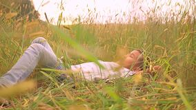 Asian joyful kid lies on wheat field with closed eyes relaxing.  stock video footage