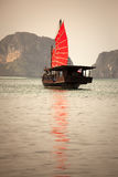 Asian junk boat. Scenic view of traditional Chinese junk boat with red sail in sea with Thailand coastline in background Stock Photography