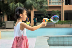 Asian kid blowing bubble Royalty Free Stock Photography