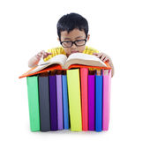 Asian kid with books isolated on white. Smart Asian boy with glasses reading a book Stock Image