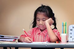 Asian kid boring when doing homework at home. Asian kid girl boring when doing homework at home Stock Photo