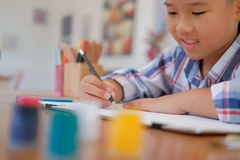 Asian kid boy child schoolboy drawing picture. children activity. Little asian kid boy child schoolboy drawing picture. children leisure activity at home royalty free stock photography
