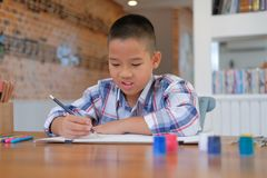 Asian kid boy child schoolboy drawing picture. children activity. Little asian kid boy child schoolboy drawing picture. children leisure activity at home royalty free stock images