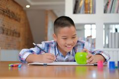 Asian kid boy child schoolboy drawing picture. children activity. Little asian kid boy child schoolboy drawing picture. children leisure activity at home royalty free stock photos