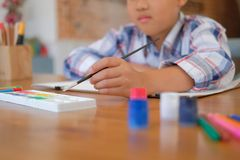 Asian kid boy child schoolboy holding paint brush drawing painting watercolor. children leisure activity at home. Little asian kid boy child schoolboy holding stock images