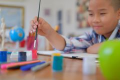 Asian kid boy child schoolboy holding paint brush drawing painting watercolor. children leisure activity at home. Little asian kid boy child schoolboy holding royalty free stock photography