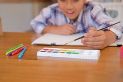 Asian kid boy child schoolboy holding paint brush drawing painting watercolor. children leisure activity at home. Little asian kid boy child schoolboy holding stock photo