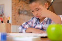 Asian kid boy child schoolboy thinking while drawing picture. ch. Little asian kid boy child schoolboy thinking while drawing picture. children leisure activity royalty free stock images