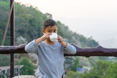 Asian kid boy is drinking water from the glass. With mountain views background.  stock photo