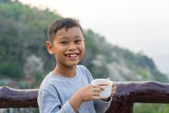 Asian kid boy is drinking water from the glass. With mountain views background.  stock images