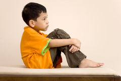 Asian kid contemplating. An asian kid is contemplating what to do next stock photo