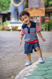 Asian kid with curly hair looking pose when being photographed. With bright emotions smiling Royalty Free Stock Image