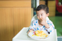 Asian kid eating birthday cake with cream on face. Stock Photography