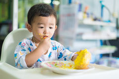 Asian kid eating birthday cake with cream on face. Royalty Free Stock Images