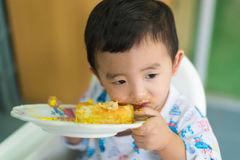 Asian kid eating birthday cake with cream on face. Royalty Free Stock Photo