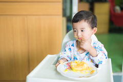 Asian kid eating birthday cake with cream on face. Royalty Free Stock Image