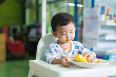 Asian kid eating birthday cake with cream on face. Stock Image