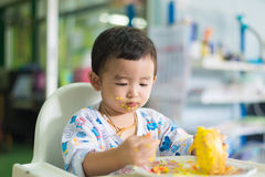 Asian kid eating birthday cake with cream on face. Royalty Free Stock Photos