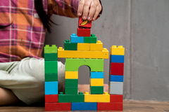 Asian kid girl building house. From plastic blocks , banana plastic block on top royalty free stock images